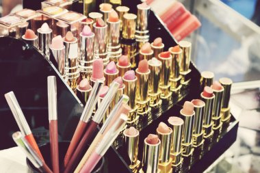 Set of colorful lipsticks with other cosmetics on a dressing table