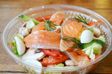 Healthy salad with salmon and quail eggs in plastic bag
