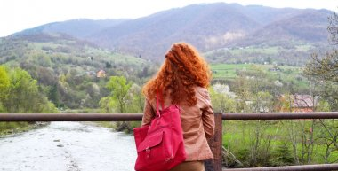 Red haired woman looking at the mountains with her back to the camera