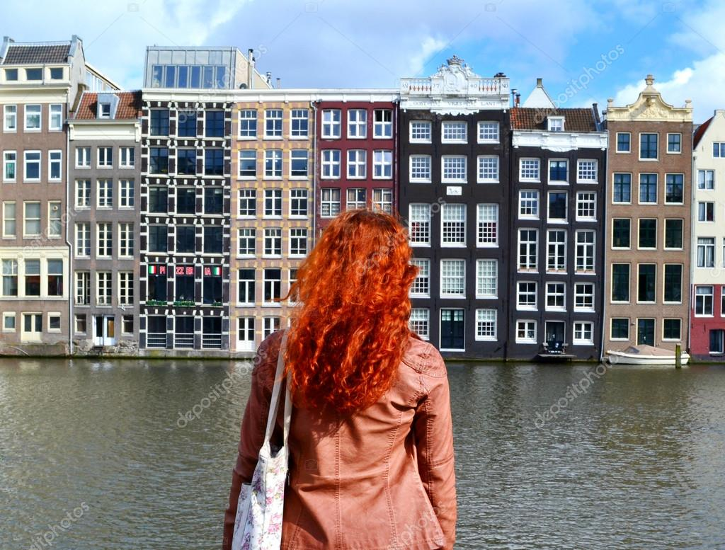 Redheaded woman in leather jacket standing with her back to the camera and looking at traditional buildings of Amsterdam city near the canal and boats