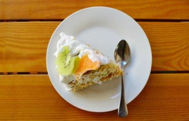 Slice of fruit cake with cream, kiwi and orange