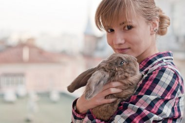 Young woman hugs cute rabbit