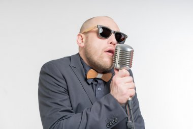 Unshaven bald man with microphone