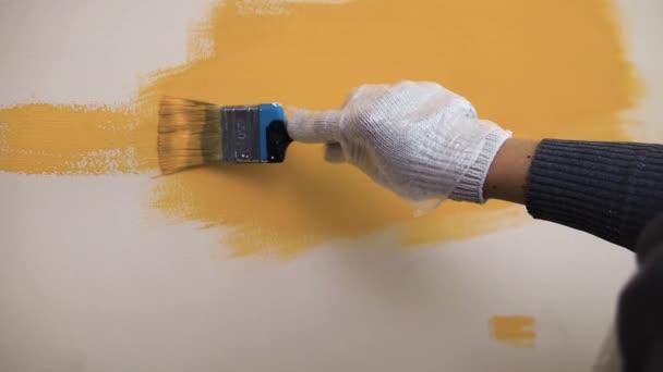 Ein Arbeiter führt einen Pinsel entlang der orangefarbenen Wand
