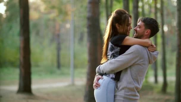 Der Mann hob seine Freundin und umarmte sie mit den Armen. Verliebtes Paar. Spazieren Sie mit Ihren Liebsten im Park