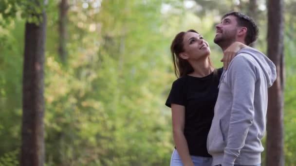 A boldog fiatal pár ölelkezik, és szerető szemekkel néznek egymásra. Családi séta a parkban. Gyönyörű szerelmespár.