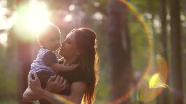 Mom holds her son in her arms and kisses him on the cheek against the backdrop of the setting sun in the park. A happy family. Mother and son