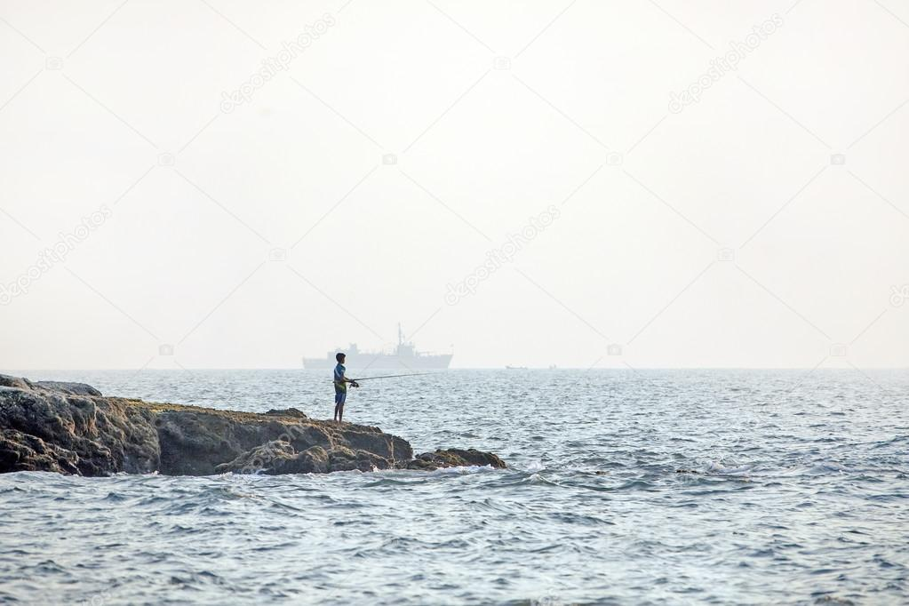 Boy fisherman and a large ship