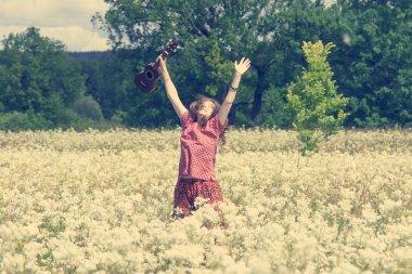 Girl on meadow with ukulele