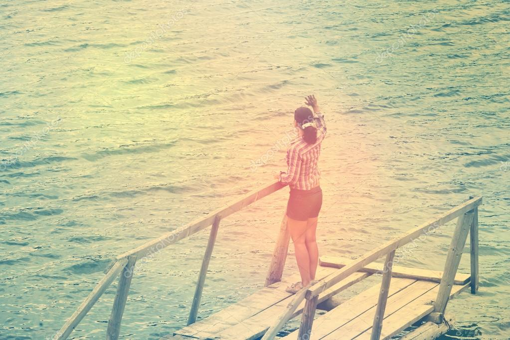 Girl staying on old wooden pier