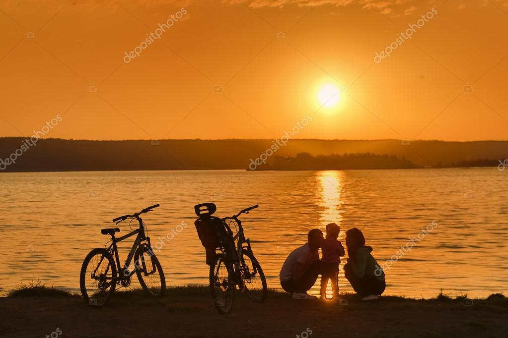 Family with bikes on riverbank
