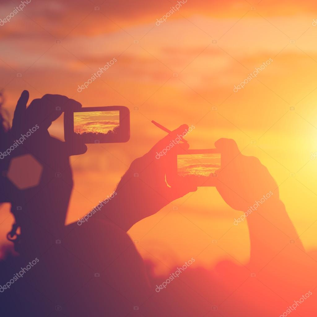 Silhouettes of people taking pictures of sunset