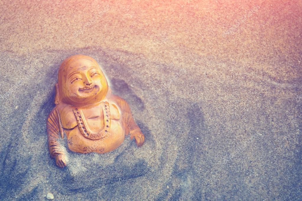 Buddha statue on sandy seacoast