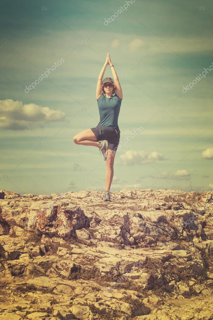 Young woman engaged in yoga on rock