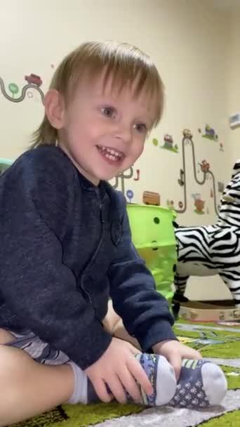 Malé světlé dítě se směje, zatímco sedí na podlaze v dětském pokoji.