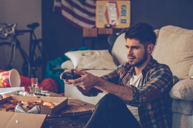 young man with joystick in messy room