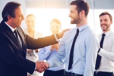 cheerful businessmen shaking hands