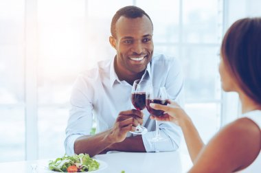 Romantic dinner.. Beautiful young African couple sitting together at the table and holding wineglasses