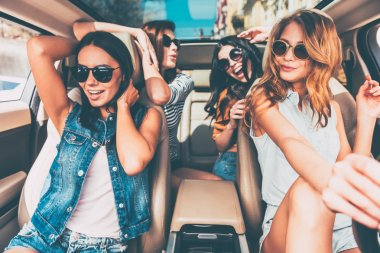 Cheerful women sitting in car