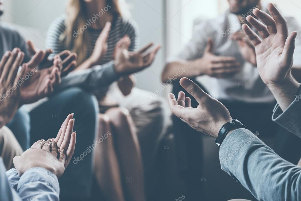 people applauding while sitting in circle together