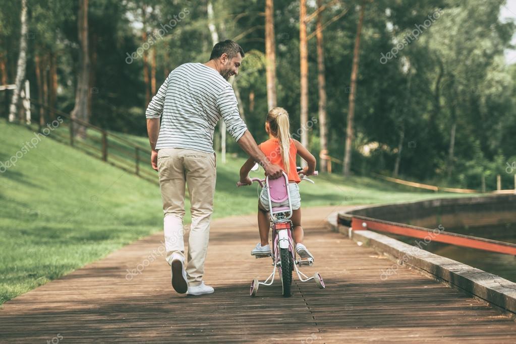 Enseñar A Los Chicos A Andar En Bici: Padre Enseñando A Su Hija A Montar En Bicicleta