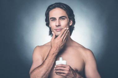 shirtless man  applying aftershave lotion