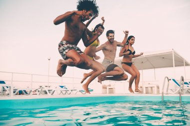 best friends jumping into swimming pool