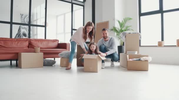 Verspielte junge Familie hat Spaß beim gemeinsamen Einzug in eine neue Wohnung