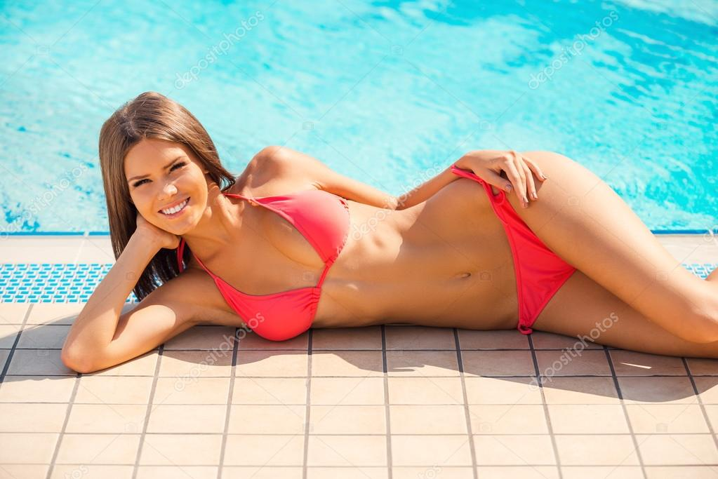 Frau im Bikini am Pool liegend — Stockfoto © gstockstudio