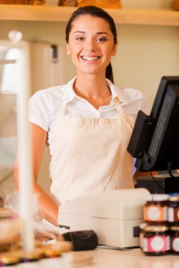 Cashier in apron standing near cash register
