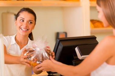 Baker giving cookies to customer