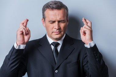 Mature man in formalwear keeping fingers crossed