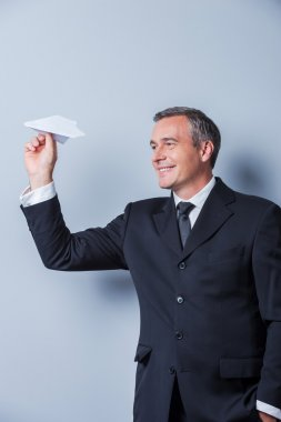 Mature man in formalwear holding paper airplane