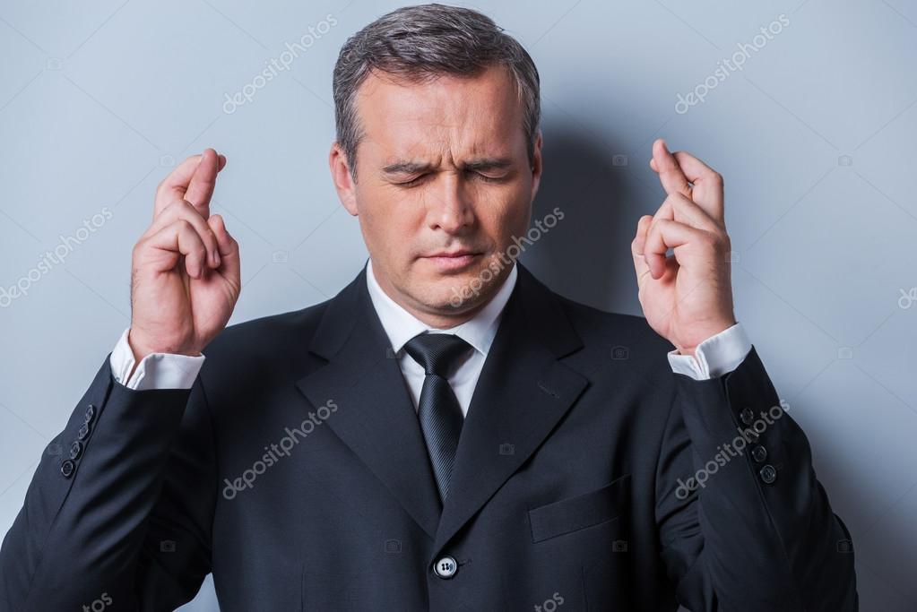 Mature man in formalwear keeping fingers crossed