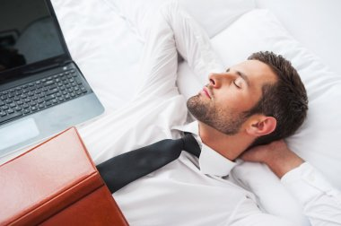 Man in shirt and tie  lying in bed at the hotel room