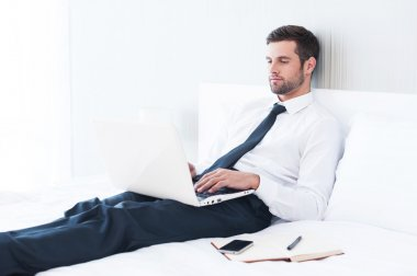 Man in shirt and tie working on laptop