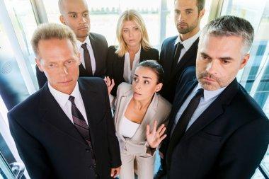 Woman in formalwear feeling trapped by the crowd in elevator
