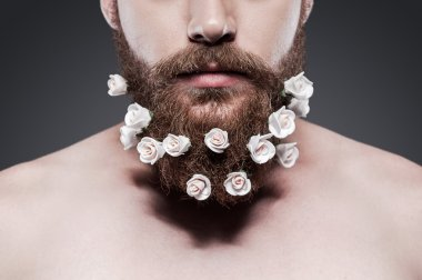 Shirtless man with flowers in his beard