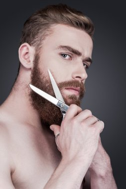 Shirtless man cutting his beard with scissors