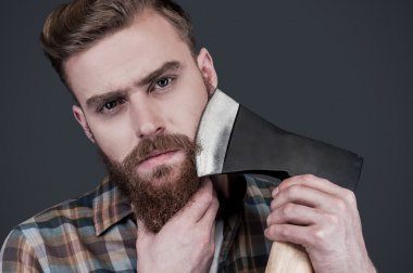 Bearded man  shaving with big axe