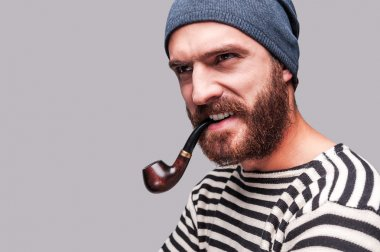 Bearded man in striped clothing smoking a pipe