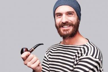 Bearded man in striped clothing holding a pipe