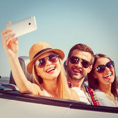 Photo People in convertible and making selfie