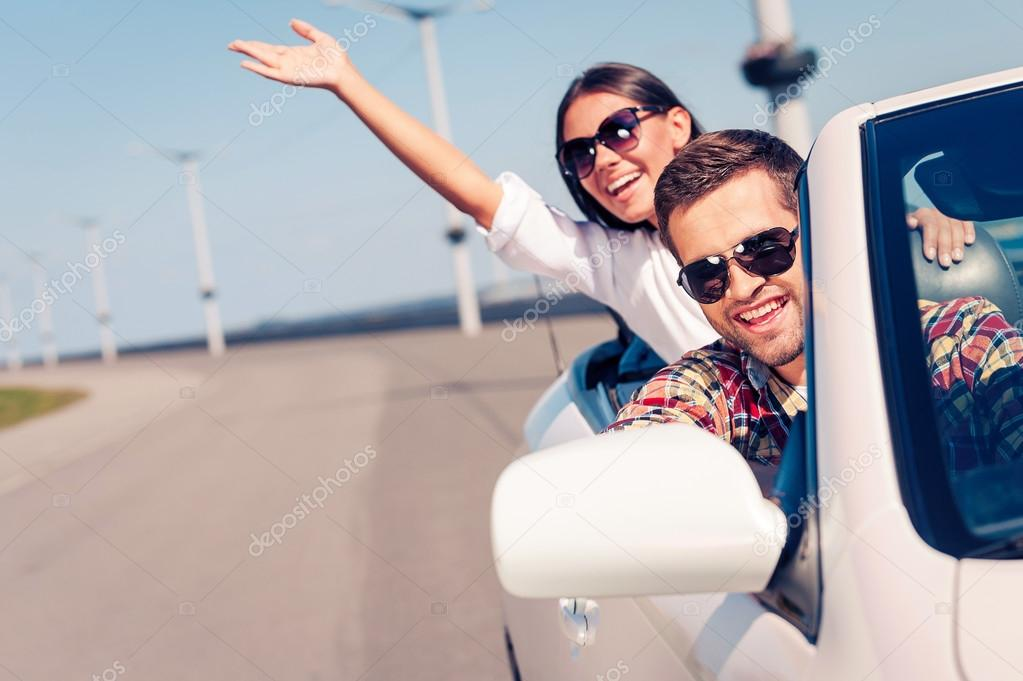Couple enjoying trip in convertible