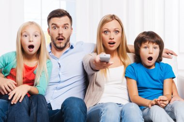 Surprised family watching TV at home