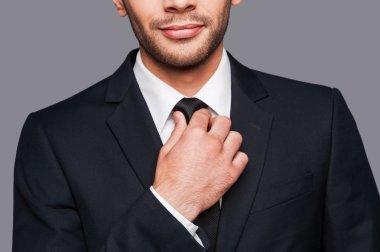 Man in formalwear adjusting his necktie