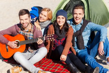 Happy people sitting near the tent with guitar