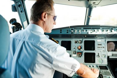 Confident male pilot sitting in cockpit