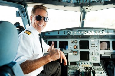 Ready to flight. Rear view of confident male pilot showing his thumb up and smiling while sitting in cockpit stock vector