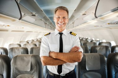 This is my plane. Confident male pilot in uniform keeping arms crossed and smiling while standing inside of the airplane stock vector